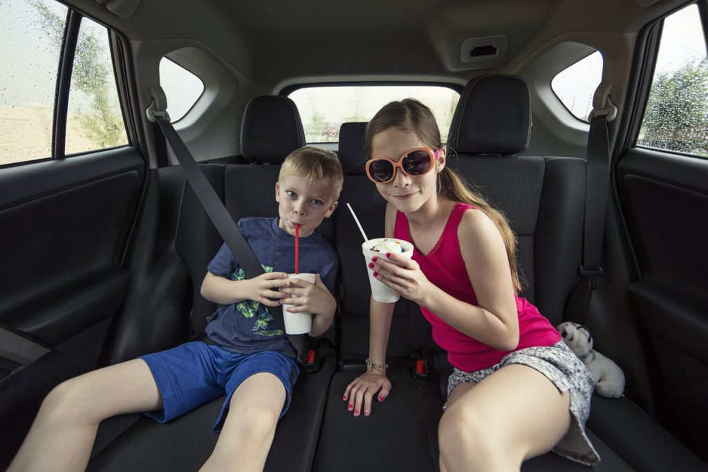 Two kids sitting in the back seat of their car eating an ice cream treat milkshake. Smiling and enjoying a sweet treat while sitting in their family automobile