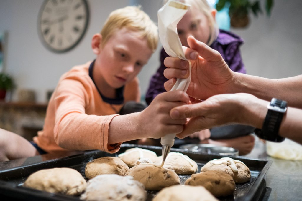 Kids help decorate the hot cross buns before the Easter celebration. Baking at home during lockdown