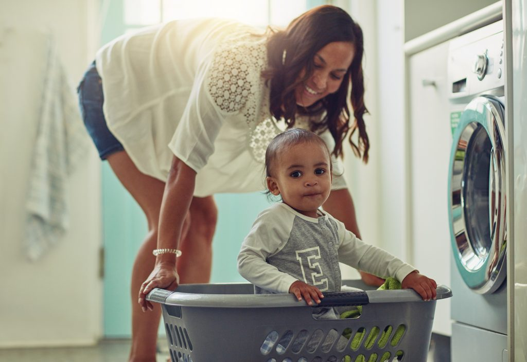 Shot of a mother and her adoarable baby boy doing the laundry at home