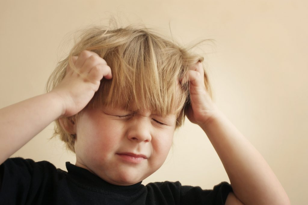 A little boy running his hands through his hair like he may be itchy.
