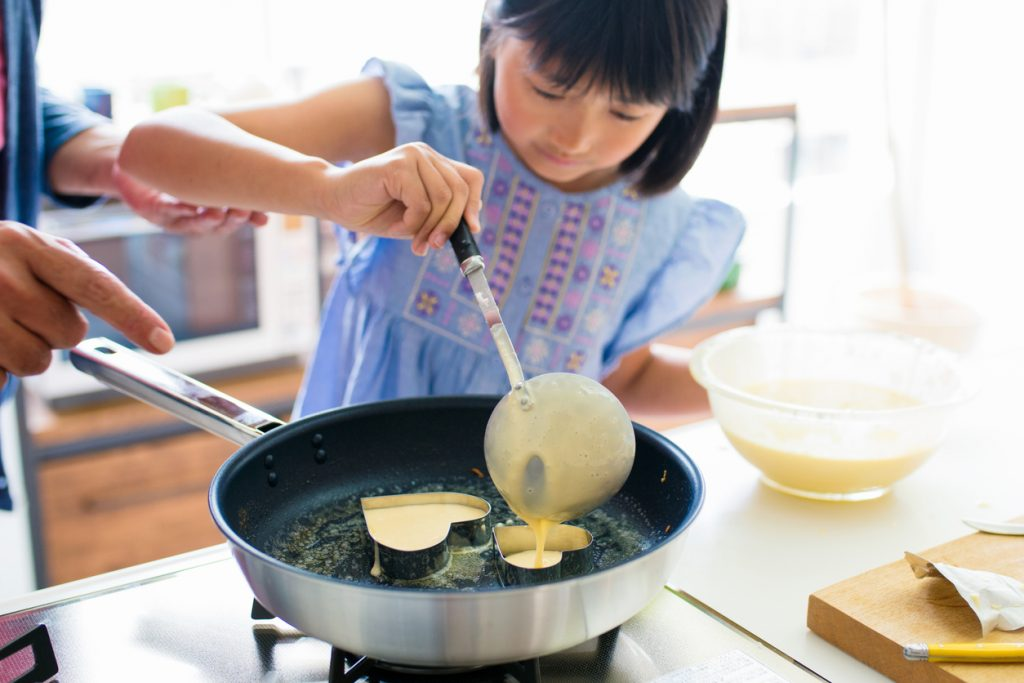 Grandfather teaching his granddaughter to cook, making heart shaped pancakes together. Kyoto, Japan. May 2016