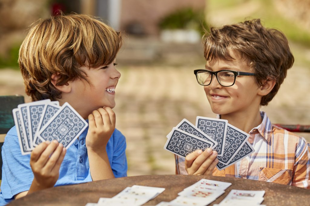 Smiling brothers playing cards at table in yard