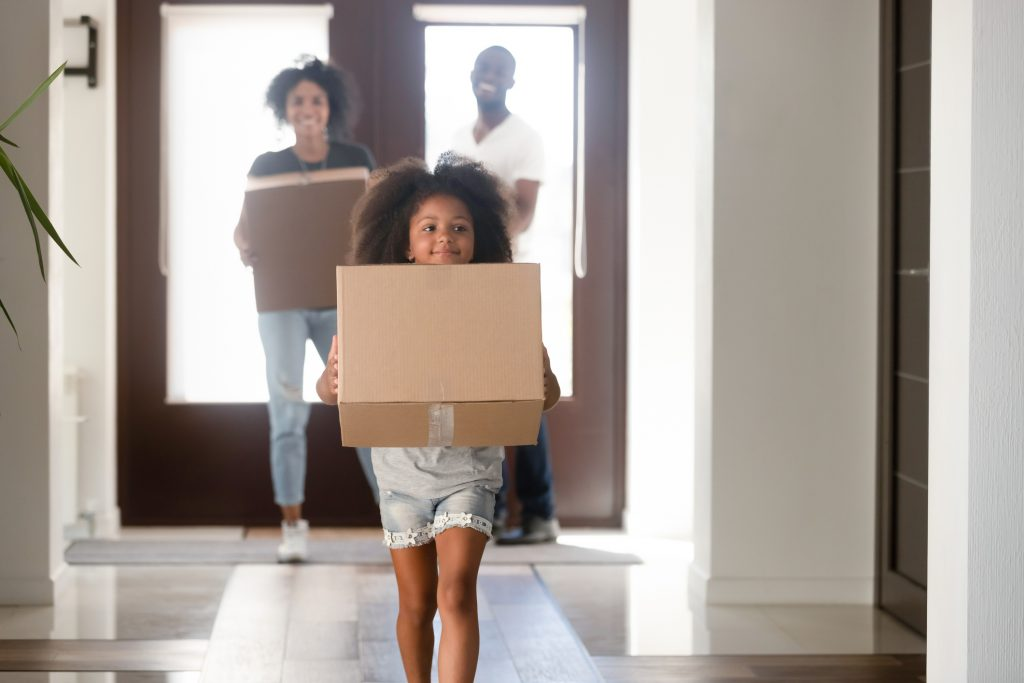 Happy small African American girl holding cardboard box run into new house, young black family moving into bought apartment, excited daughter carry personal belongings to home.