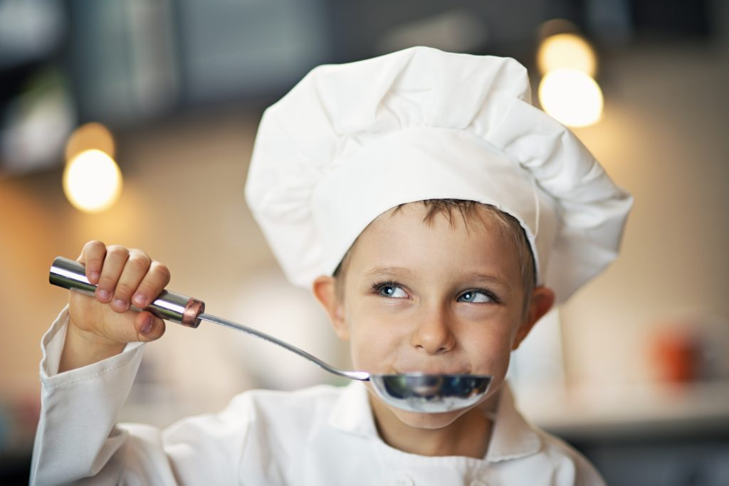 Little boy dressed up as chef tasting soup. The boy aged 4 is smiling and looking away. The soup is tasting great!