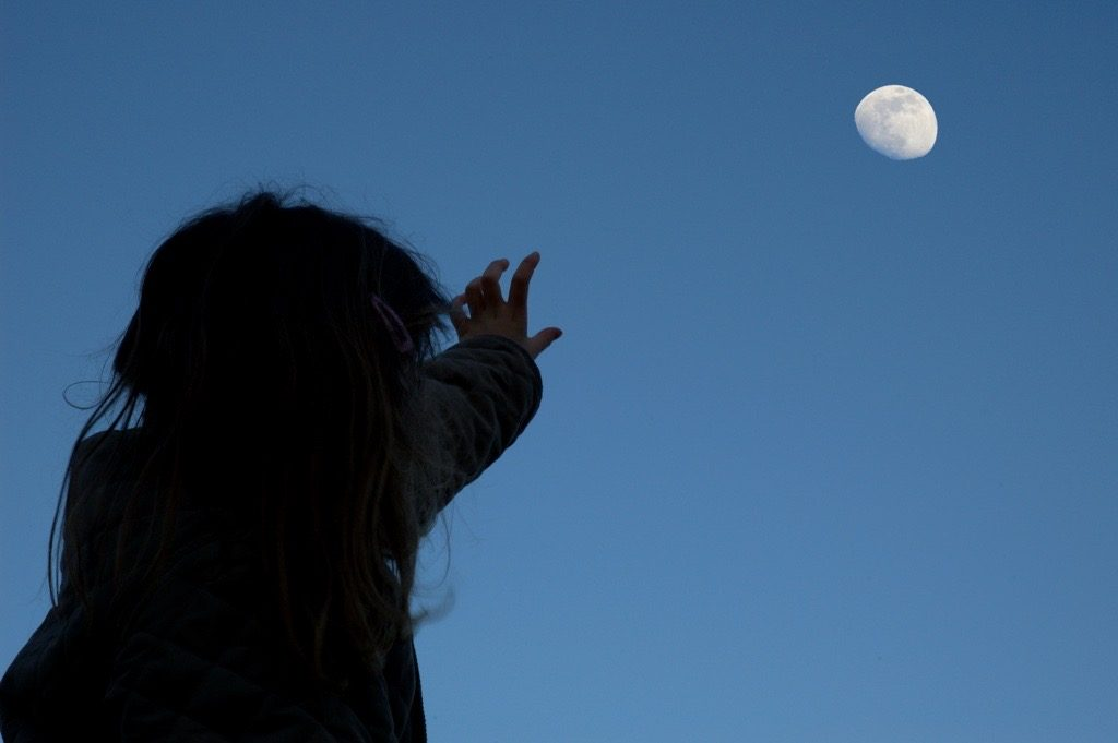 A girl at night reaching toward the moon with one hand.