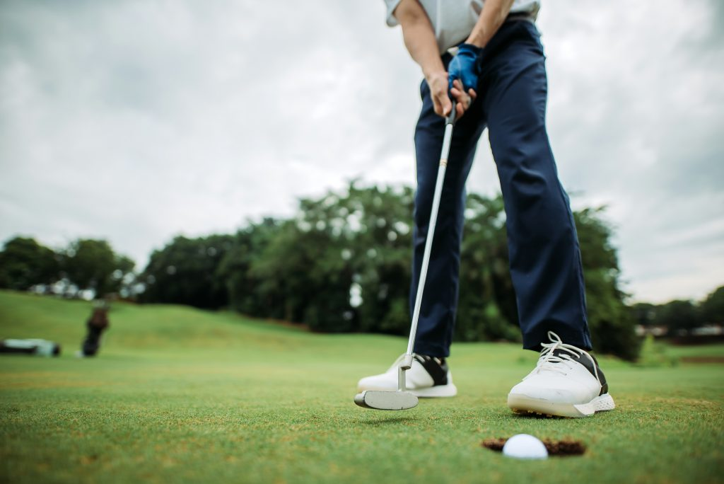 A man playing golf just as he is hitting the ball into the hole