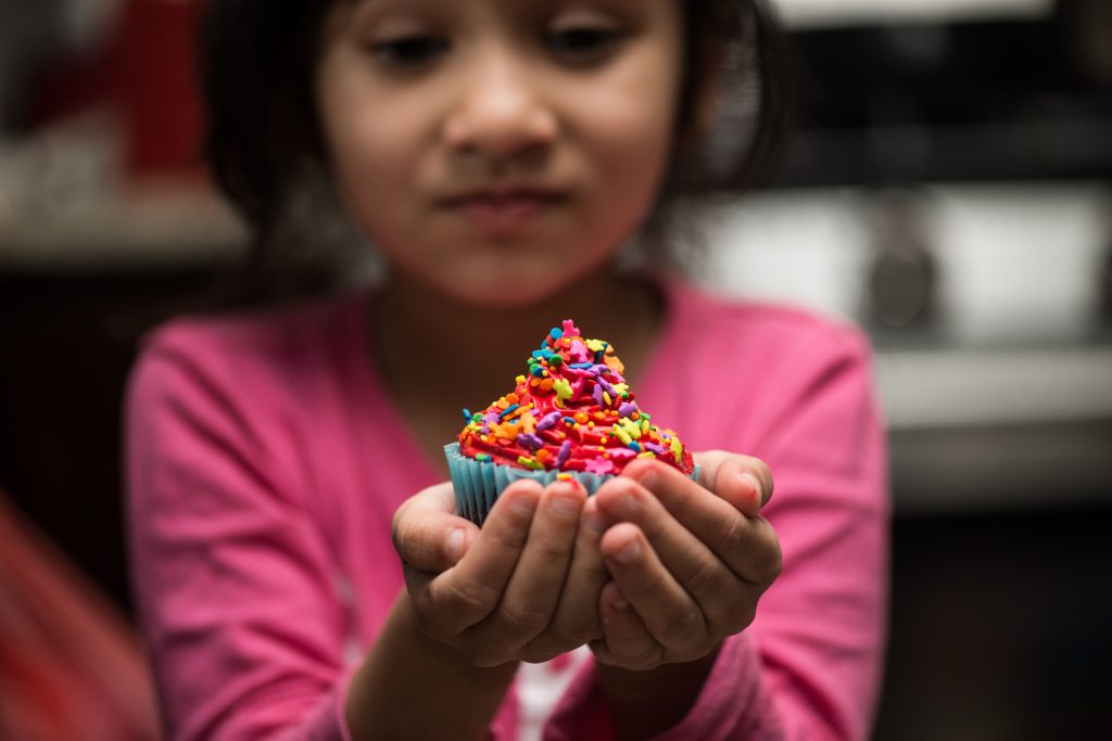 A little girl carefully holding a brightly sprinkled cupcake in her hands.