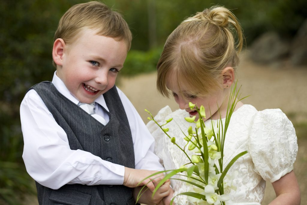 A little boy and a little girl laughing in their wedding outfits.