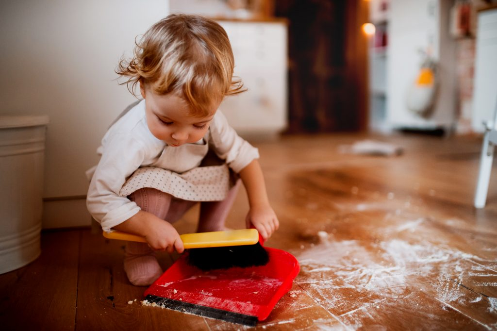 A little toddler girl sweeping up flour that's all over a wood floor